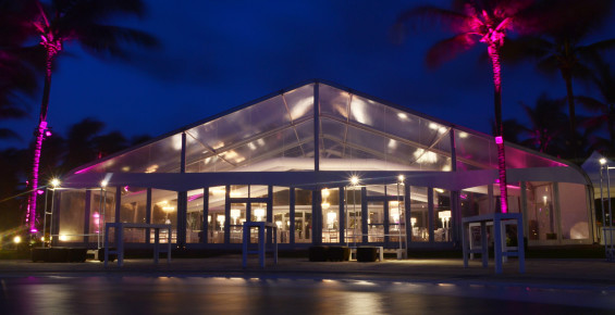 Outside Fastrack 062 clear tent with glass walls at mexican resort on the beach lit from the inside at night.